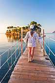 Young woman walking on a hanging wooden bridge over the sea leading to Cameo Island, Agios Sostis, Zakynthos, Ionian Islands, Greece, Europe