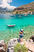 Young woman with a straw hat and a turquoise dress admiring the turquoise sea at Limeni, Mani region, Peloponnese, Greece, Europe