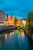 Light trail of a touristic boat and triple bridge lights reflected on Ljubljanica river. Ljubljiana, Osrednjeslovenska, Slovenia