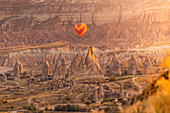 Hot air balloons at sunrise over fairy chimney of Goreme. Rose valley, Goreme, Capadocia, Kaisery district, Anatolia, Turkey.