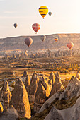 Hot air balloons over the rock tuff formations of Goreme. Capadocia, Kaisery district, Anatolia, Turkey.