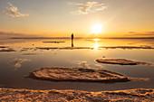 A tourist admiring sunset along the beach of Tuz Golu salt lake. Sereflikochisar, Ankara district, central Anatolia, Turkey.