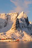 Rote Häuser und Berge in Reine von der gegenüberliegenden Seite der Bucht bei Sonnenaufgang, Reine, Lofoten, Norwegen, Skandinavien, Europa