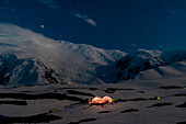 Nightscape of peak Lenin camp one with Peak Lenin massif in the background under a starring sky. Pamir, Kyrgyzstan, Central Asia.