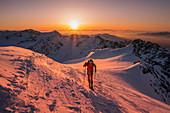 Ski mountaneer in backlight at sunrise into the summit of San Matteo mount. San Matteo peak, Forni glacier, Santa Caterina Valfurva, Valtellina, Sondrio district, Alps, Lombardy, Italy, Europe.