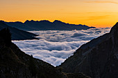 Mountain sunrise with cloudy carpet in foreground and Tonale peaks in background. Casola pass, Ponte di Legno, Alps, Brescia district, Lombardy, Italy, Europe.