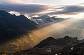 Ray of light from italian Alps during a backlight sunrise. Campana peak, Valgrosina valley, Grosio, Valtellina, Sondrio district, Lombardy, Italy, Europe.