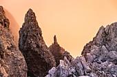 Felsvorsprünge während eines wolkigen Sonnenuntergangs im Gegenlicht unter dem Berg Roda de Vael in der Rosengartengruppe, Karezza, Fassatal, Dolomiten, Trentino-Südtirol, Italien, Europa