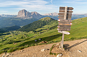 Trail signpost at Seceda, with Langkofel and Plattkofel in the background. Ortisei, Bolzano province, Trentino Alto Adige, Italy.