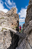 Young woman standing on a wooden bridge on the via ferrata on Mount Paterno, in summer. Sesto Dolomites, Trentino Alto Adige, Italy.