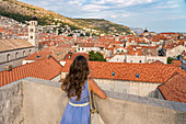 Woman staring at the red roofs of the town from the old walls. Dubrovnik, Dubrovnik - Neretva county, Croatia.