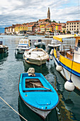 Fishing boats at the harbour with the old town in the background. Rovinj, Istria county, Croatia.