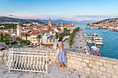Woman admiring the old town and seafront from Karmelengo castle, in summer. Trogir, Split - Dalmatia county, Croatia.
