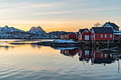Typical fishermen red houses reflected on the sea at dawn in winter. Svolvaer, Nordland county, Northern Norway region, Norway.