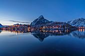 Reine Bay at dusk in winter, with Olstinden peak in the background. Reine, Nordland county, Northern Norway, Norway.