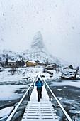 Woman walking on a wooden bridge under the snow, looking towards Hammarskaftet. Reine, Nordland county, Northern Norway, Norway.