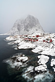 Hamnoy village under the snow, with Festheltinden peak in the background. Moskenes municipality, Nordland county, Northern Norway, Norway.