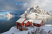 Traditional 'rorbu' houses with Olstinden peak in the background in winter. Reine, Lofoten district, Nordland county, Northern Norway, Norway.