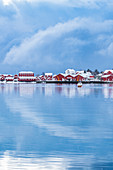 Traditional 'rorbu' houses reflected on the fjord in winter. Reine, Lofoten district, Nordland county, Northern Norway, Norway.