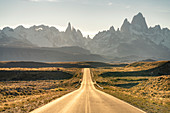 Road leading to El Chalten, with Fitz Roy range in the background at sunset. El Chalten, Santa Cruz province, Argentina.