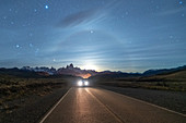Car driving on the road leading to El Chalten, with Fitz Roy range and moonlight in the background at night. El Chalten, Santa Cruz province, Argentina.