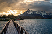Wooden bridge on Lake Pehoé with Cerro Paine Grande in the background at sunset. Torres del Paine National Park, Ultima Esperanza province, Chile.