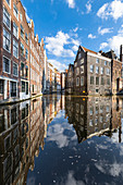 Typical houses reflected on canals in De Wallen district in Amsterdam (North Holland, Netherlands)
