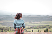 A girl watching the countryside from Sant'Angelo in Colle, Siena, Tuscany, Italy, Europe
