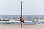 Backpacks hang on a pole in the North Sea, St. Peter-Ording, North Sea, North Friesland, Germany