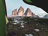 Italy, South Tyrol, Bolzano, Dolomites, Sexten Dolomites, Drei Zinnen/Tre Cime di Lavaredo at sunrise from a tent.