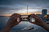 A man photographs the pier of Ponta Delgada Marina at sunset\n, Ponta Delgada, Sao Miguel, Azores, Portugal, Western Europe\n