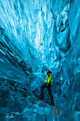 Man stands an ice cave of Breidamerkurjokull, Austurland, Iceland, Northern Europe