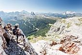 a climber along the via ferrata Lipella on the Tofana di Rozes is looking at the landscape around her, Belluno province, Veneto, Italy