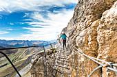A climber along the via ferrata Piazzetta on the Sella Group, Bolzano province, South Tyrol, Trentino Alto Adige, Italy