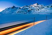 The Bernina Express passes on the shores of Lake Bianco at the blue hour. Canton of Graubunden. Engadine. Switzerland. Europe