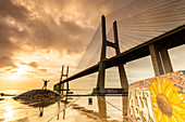 A person enjoying a colorful sunrise at the Skatepark Expo, in front of the Vasco da Gama bridge. Lisbon, Portugal, Europe.