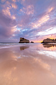 A colorful sunset reflected on the wet shores of Praia Dos Tres Irmaos. Alvor, Portimao, Algarve, Portugal,Europe.
