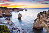 View of the famous natural arches in Praia da Marinha at sunrise. Caramujeira, Lagoa, Algarve, Portugal, Europe.