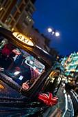 England, London, Kinghtsbridge, London Taxi on Brompton Road, dusk