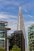 United Kingdom, London, Southwark district, the banks of the River Thames near Tower Bridge, the skyscraper The Shard by architect Renzo Piano, office buildings, airplane in the sky
