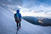 GUIDE LEADING HIS ROPED PARTY AT SUNRISE ON AN ICY SLOPE TO THE CASTOR, MONTE ROSA, GRESSONEY-LA-TRINITE, AOSTA VALLEY, ITALY