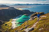HIKER AT THE SUMMIT OF MOUNT MATIND ABOVE THE WHITE SAND BEACHES AND TURQUOISE WATERS OF THE ISLAND OF ANDOYA, NORWAY
