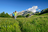 Man and woman hiking through meadow, Monte Camicia in the background, Campo Imperatore, Gran Sasso, Gran Sasso National Park, Parco nazionale Gran Sasso, Apennines, Abruzzo, Italy