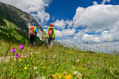 Man and woman hiking through flower meadow, Grande Anello dei Sibillini, Sibillini Mountains, Monti Sibillini, National Park Monti Sibillini, Parco nazionale dei Monti Sibillini, Apennines, Marche, Umbria, Italy