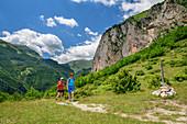 Man and woman hiking under rock face, Grande Anello dei Sibillini, Sibillini Mountains, Monti Sibillini, National Park Monti Sibillini, Parco nazionale dei Monti Sibillini, Apennines, Marche, Umbria, Italy