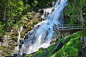 Several people stand on the viewing platform in front of the Sintersbach waterfall, Sintersbach waterfall, Kitzbühel Alps, Tyrol, Austria