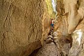 Woman hiking through canyon Gorges de Regalon, Gorges de Regalon, Luberon Natural Park, Vaucluse, Provence-Alpes-Cote d'Azur, France
