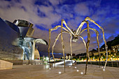 Illuminated Guggenheim Museum, architect Frank O. Gehry, with sculpture Spider, artist Louise Bourgeois, Bilbao, Basque Country, Spain