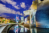 Illuminated Guggenheim Museum, architect Frank O. Gehry, with Puente La Salve bridge in the background, Bilbao, Basque Country, Spain