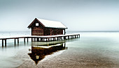 Boathouse during snowfall on Lake Starnberg, Tutzing, Bavaria, Germany
